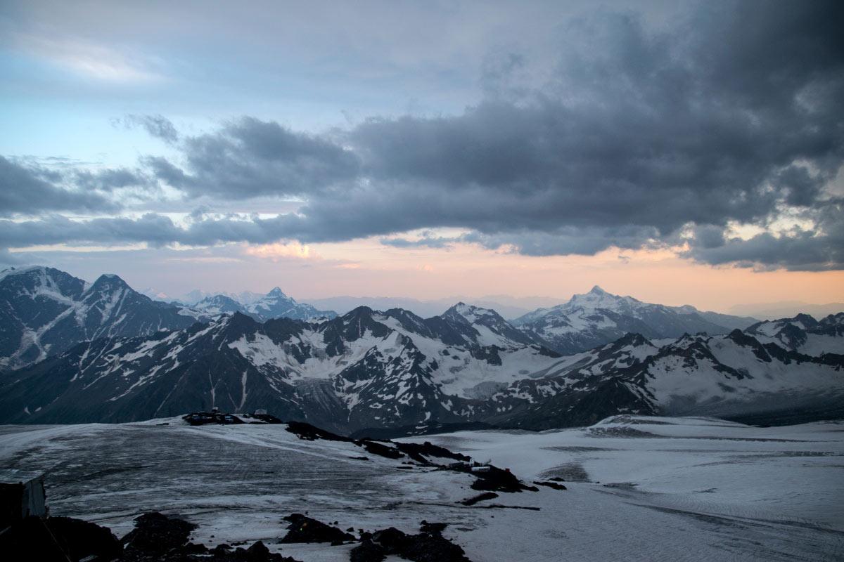 Kaukaz, aj vdnešnej dobe, predstavuje pre väčšinu z nás zmes exotiky, romantických predstáv atajuplnosti. Preto si veľmi radi prečítame zážitky dobrodruhov, ktorí sa rozhodli preskúmať tieto vzdialené končiny aj za nás. Marek Kochan si splnil svoj sen ozdolaní Elbrusu, najvyššieho vrcholu Kaukazu aEurópy. Prinášame vám jeho pútavú reportáž z tejto výpravy. Zároveň sme radi, že máme aj inú referenciu ako naše testovanie značky Black Hill Outdoor, ktorého výsledok uvidíte čoskoro :) Môj sen oKaukaze sa mi podarilo splniť vauguste 2017. Predchádzalo mu dlhé plánovanie, príprava trasy, stravy avýstroja. Veci na Kaukaz som vyberal na základe cestopisov na webe, zisťoval som informácie aj u konkrétnych ľudí, ktorí tam už boli. Veľmi dôležitou časťou bolo oblečenie. Vedel som, že tam už treba oblečenie brať naozaj vážne, počasie je tam skutočne nevyspytateľné aj v lete. Potreboval som hlavne niečo odolné proti mechanickému poškodeniu - nekupoval som len na Kaukaz, ale aj na výskumy pralesov, ktorých sa zúčastňujem a tam treba fakt odolné veci. Tiež som samozrejme hľadal niečo, čo ma nezradí v mraze ani vlhku. Pri zháňaní oblečenia som úplnou náhodou vjednom obchode vBrezne porozprával osvojich plánoch majiteľovi obchodu aon mi hneď ponúkol spoluprácu. Presvedčil ma ovýhodách merino vlny, ktoré som si následne preveril aj na webe. Bolo mi sympatické, že Black hill outdoor je slovenský výrobok aso zakladateľom značky zdieľam lásku kprírodným atradičným materiálom. Konečne sme spolu s parťákom, Čechom Zdeňkom, vyrazili z Viedne do mesta Minerálne Vody, vstupnej brány Kaukazu. Odtiaľ nás cesta zaviedla úchvatným údolím dravej horskej rieky Baksan až pod majestátny Elbrus. Prvú noc sme strávili vkempe, vdedinke Terskol, na úplnom konci doliny. Po krátkom spánku, ešte unavení zcesty, sme sa vydali lanovkou na vrch Čeget. V nadmorskej výšky 3000 metrov sme si prvýkrát užili nádherné výhľady na oproti stojaci velikán Elbrus, jeho rozľahlosť a ohromujúcu výšku. Tam sme si plne uved