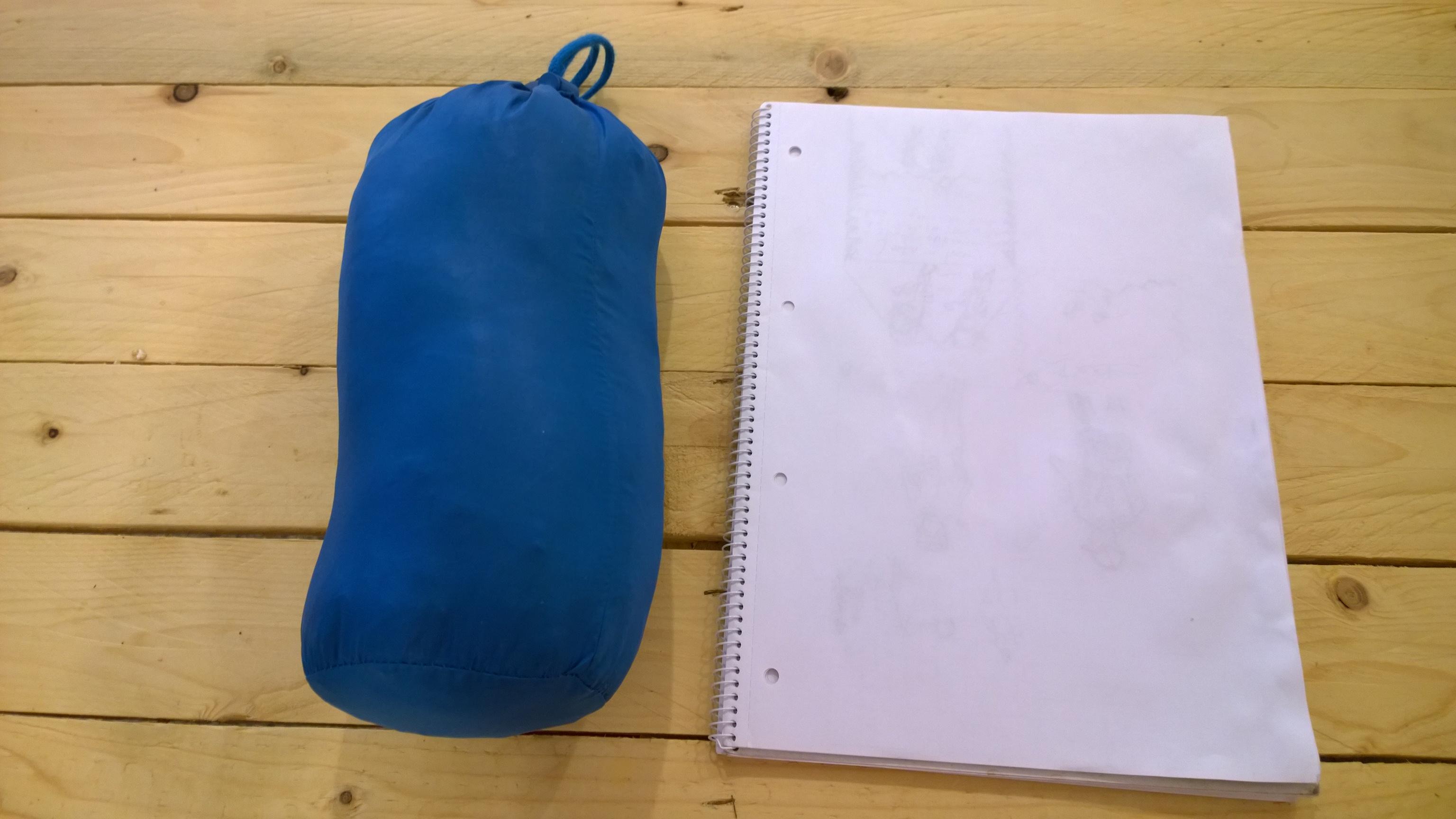 Karrimor páperová bunda zbalená vo vrecku, na porovnanie veľkosti vedľa A4 zápisníku