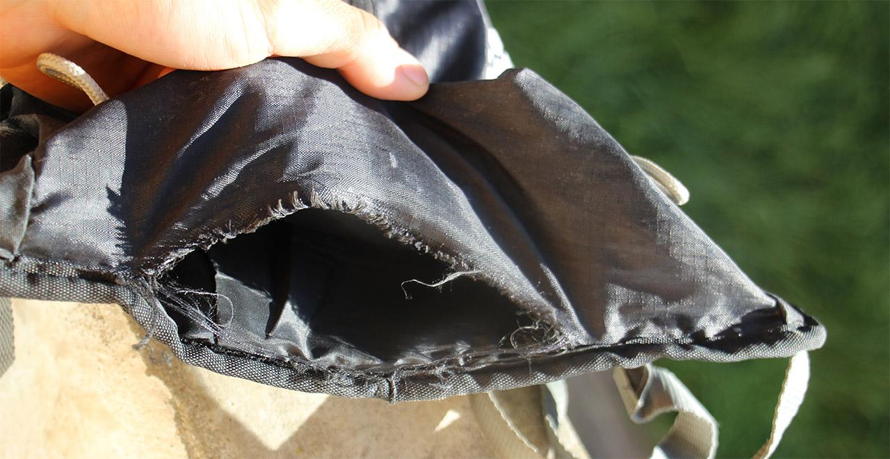 Rozpadnutý spodok batoha, už mimo možnosť záchrany - pekne je vidno páranie tkaniny